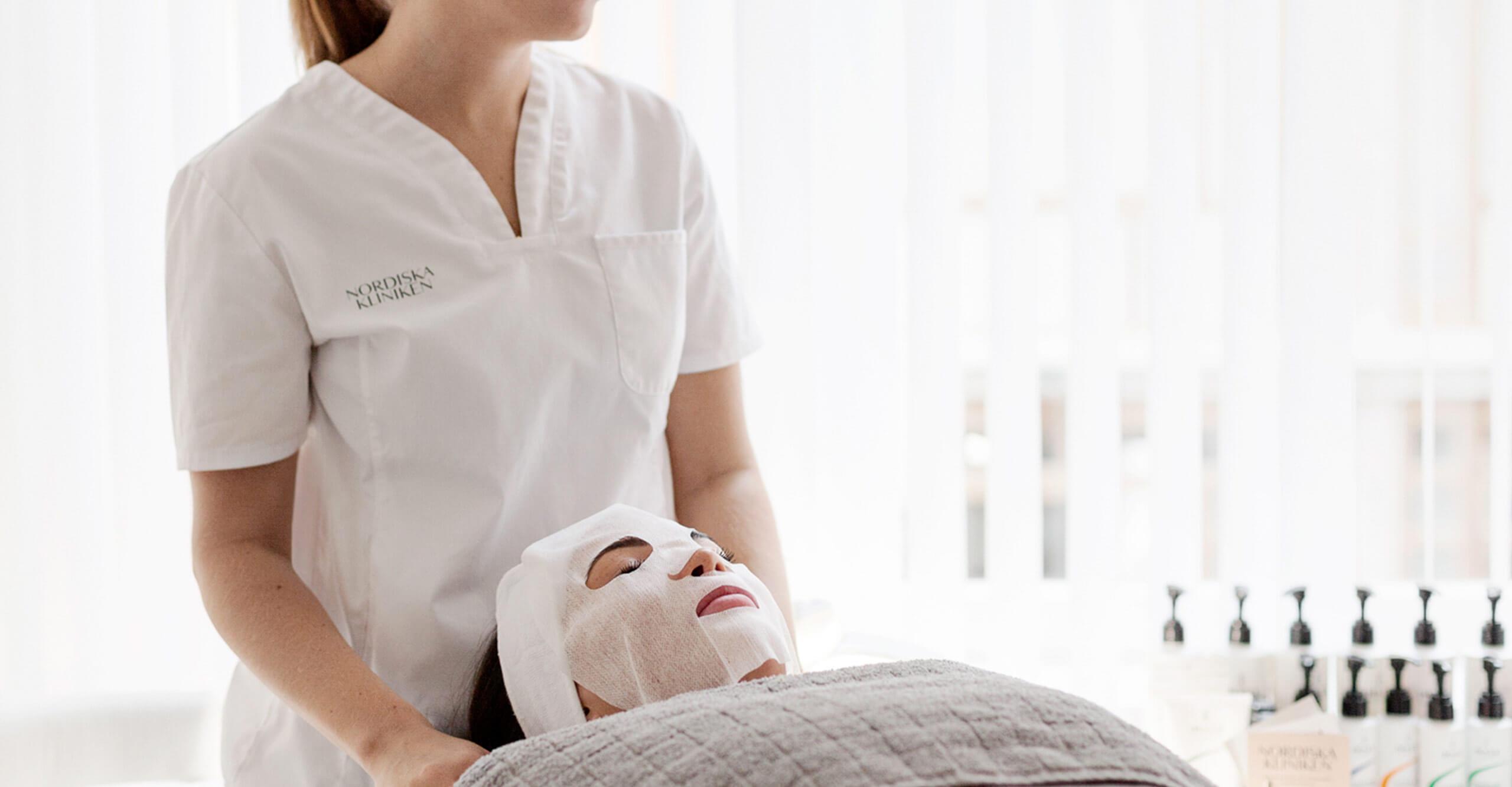 Ansiktsbehandling med ansiktsmask genomförs av en hudterapeut