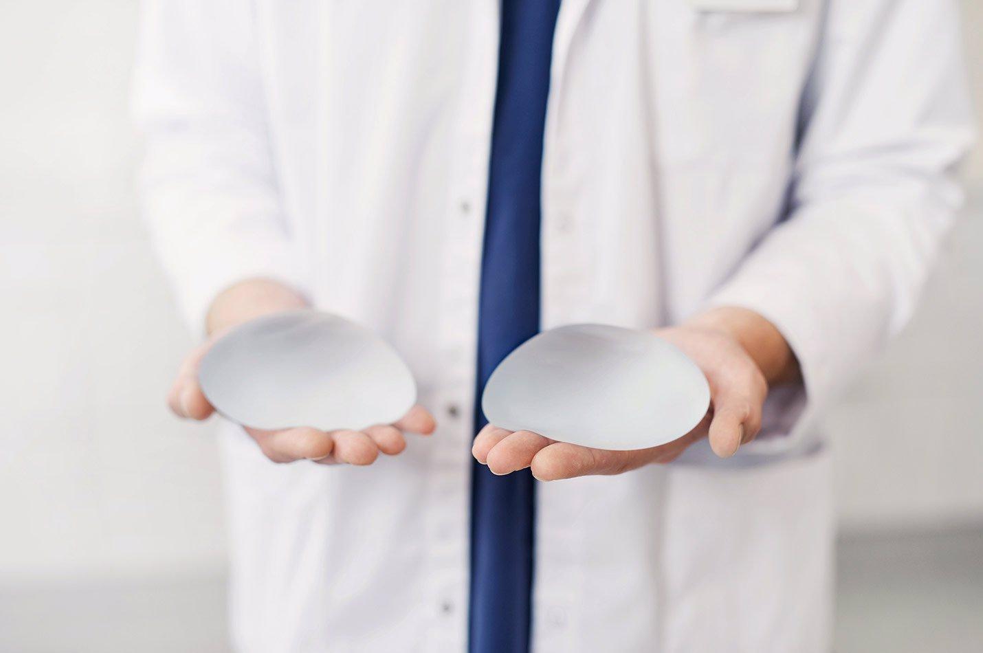 Plastikkirurg håller i Bröstimplantat till bröstförstoring